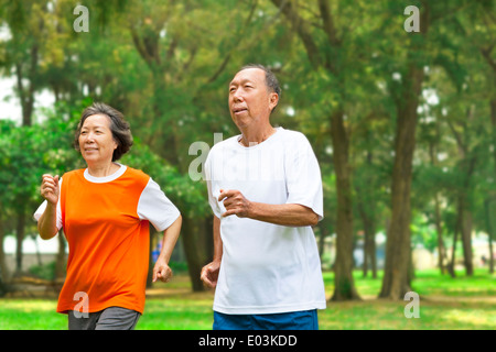 happy senior couple running together in the park - Stock Photo