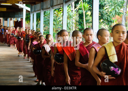 Buddhist novices lining up for lunch. - Stock Photo