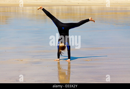 Twelve year old girl in wetsuit performing a cartwheel on a sandy beach in summer - Stock Photo