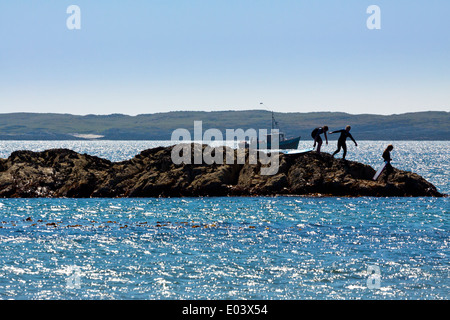Children playing on rocks on a beach on Isle of Coll Inner Hebrides Argyll and Bute Scotland UK with fishing boat - Stock Photo