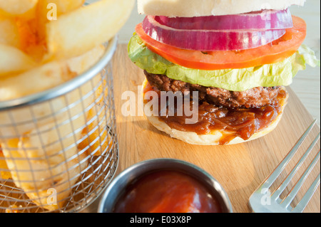 Classic burger and salad with side order of French fries or chips and tomato ketchup on a wooden plate - Stock Photo