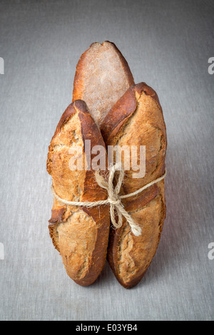 A display of breads tied up with a length of string (France). Présentation de pains liés avec une ficelle (France). - Stock Photo