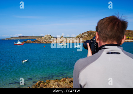 Man taking a photograph of the stunning views at St Agnes and Gugh, Isles of Scilly, Scillies, Cornwall in April - Stock Photo