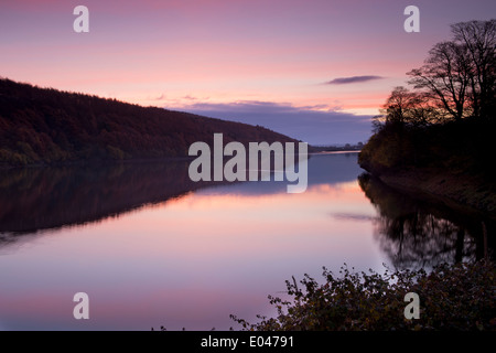 Beautiful scenic morning sunrise over still, calm water & woodland at rural, deserted Lindley Wood Reservoir, Washburn - Stock Photo