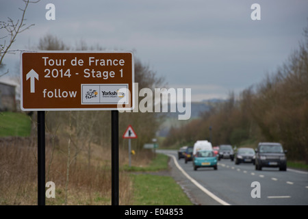 Close-up of brown tourist roadside sign marking route of Tour de France, with vehicles driving along country road - Stock Photo