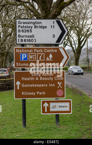 Car approaching 4 different traffic road signs, 1 above the other, pointing & giving directions (3 brown for tourists) - Stock Photo