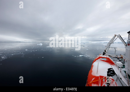 expedition ship with lifeboat covered in snow moored in Fournier Bay on Anvers Island Antarctica - Stock Photo