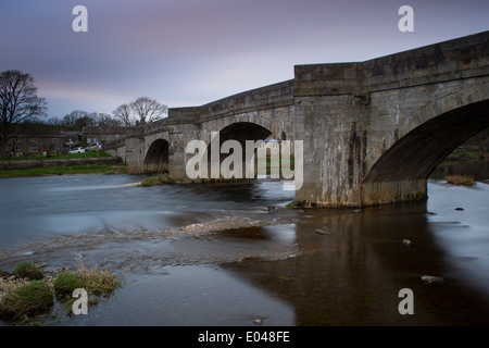 View of stone bridge spanning River Wharfe flowing through Burnsall village on a spring evening under blue pink - Stock Photo