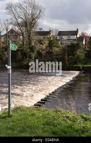 Public footpath sign pointing to partially covered stepping stones crossing flowing river - River Wharfe near Ilkley, - Stock Photo