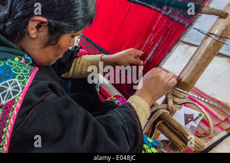 Indigenous female weaver weaving on a traditional loom in Sucre, Bolivia. - Stock Photo