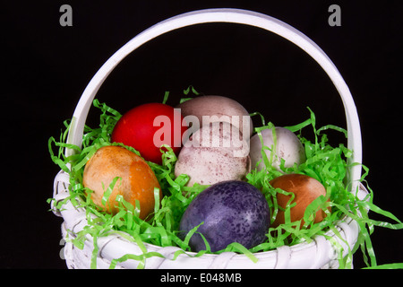White wicker basket filled with multi-hued easter eggs - Stock Photo