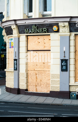 The Mariner, a closed and boarded up pub restaurant business in Brighton - Stock Photo