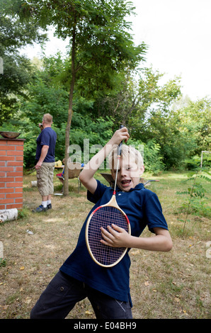 Polish boy age 10 playing air badminton guitar while father works at grill. Zawady Central Poland - Stock Photo