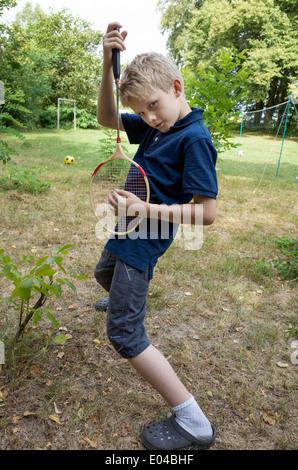 Polish boy age 10 playing air guitar with a badminton racquet. Zawady Central Poland - Stock Photo