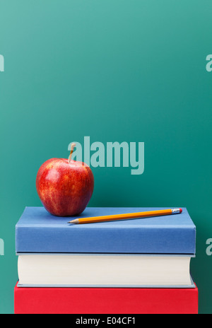 Chalk Board Apple and Books in a Classroom Setting with Copy Space. - Stock Photo
