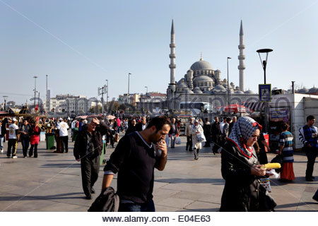 local Istanbul people near the Galata bridge with the Yeni Camii in the background - Stock Photo