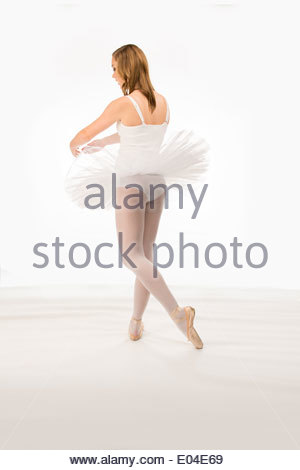 Young woman ballet dancer in a dance pose in a white tutu on a white background - Stock Photo
