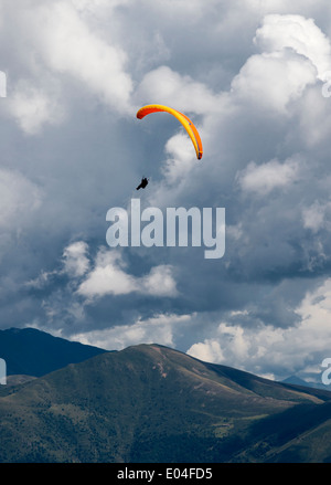 Yellow paraglider flying in the alps - Stock Photo
