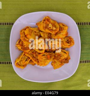 Cappellacci with ragù; pasta stuffed with pumpkin (Famous dish in Ferrara) - Stock Photo