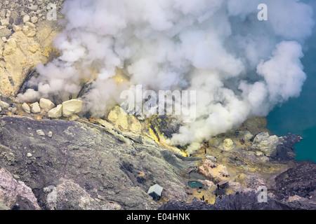 Sulfur mine near turquoise acid crater lake, Kawah Ijen, Banyuwangi Regency, East Java, Indonesia - Stock Photo