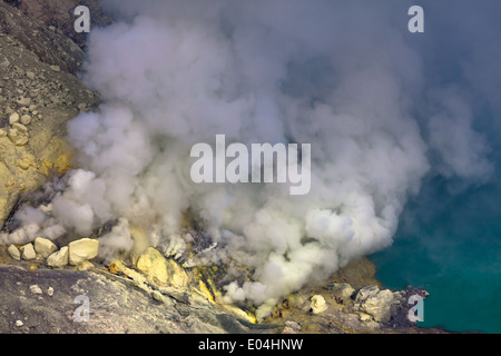 Sulfur mine near turquoise acid crater lake, Kawah Ijen, Banyuwangi Regency, East Java, Indonesia - Stock Photo