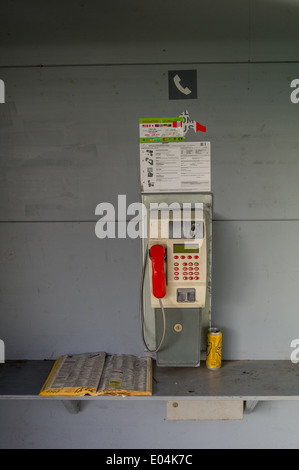 A pay phone box in a telephones. Phoning ace earlier with money and coins, Ein Muenzfernsprecher in einer Telefonzelle. - Stock Photo