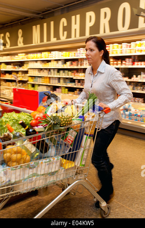 Young woman buys At the supermarket food and fruit., Junge Frau kauft im Supermarkt Lebensmittel und Obst ein. - Stock Photo