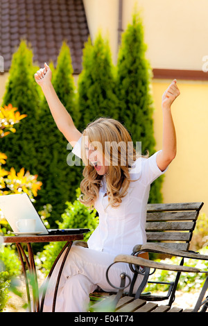 Successful, laughing woman with laptop in the guards, Erfolgreiche, lachende Frau mit Laptop im Garten - Stock Photo