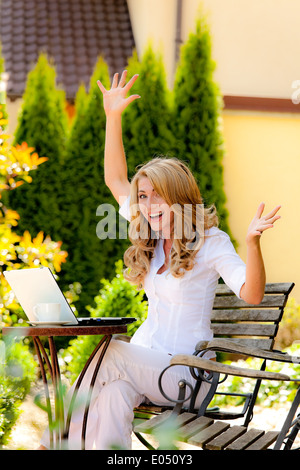 Successful, laughing woman with laptop in the garden, Erfolgreiche, lachende Frau mit Laptop im Garten - Stock Photo