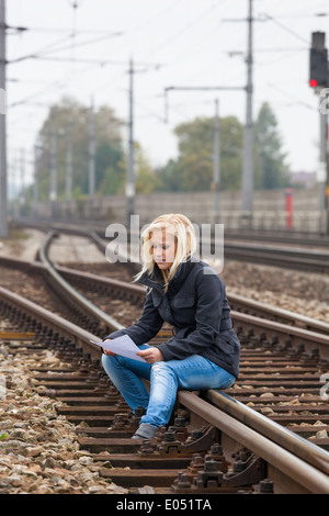 A young woman with suicide thoughts sits on a rail. If farewell letter holds in the hand and thinks about her suicide., - Stock Photo
