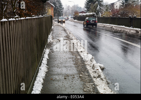 Snow on sidewalk and street, symbolic photo for accident risk and Raeumpflicht, Schnee auf Gehweg und Strasse, Symbolfoto - Stock Photo