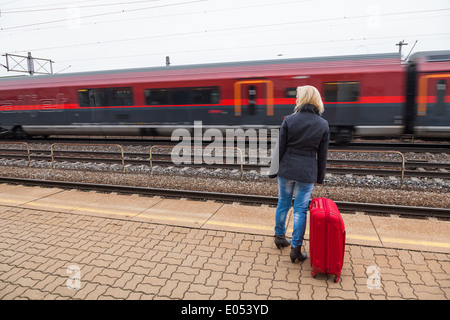 A young woman with suitcase waits on the platform of a railway station for her train. Delays, Eine junge Frau mit - Stock Photo