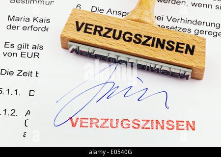 A stamp of wood lies on a document. German label: Interests on arrears, Ein Stempel aus Holz liegt auf einem Dokument. Deutsche
