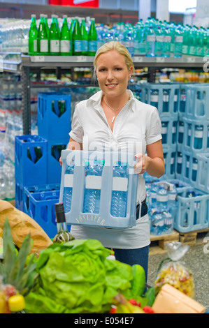 A young woman buys mineral water in the drink department at the supermarket. , Eine junge Frau kauft Mineralwasser - Stock Photo