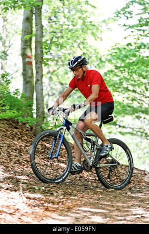 Sporty boss with Mountain bike bicycle in the wood, Sportlicher Senior mit Mountain Bike Fahrrad im Wald - Stock Photo