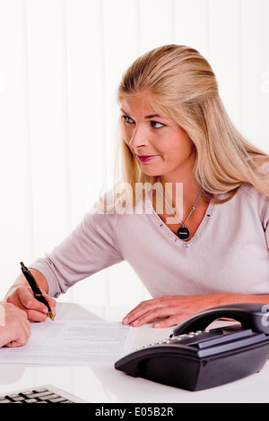 Young woman signs a contract in an office, Junge Frau unterschreibt einen Vertrag in einem Buero - Stock Photo