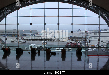 Silhouette of passenger's at Charles de Gaulle airport in Paris, sitting in chairs, watching airplanes through a - Stock Photo
