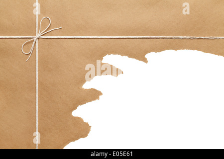 Brown Paper Package Tied with thin Rope string bow Torn Open on White Background Copy space. - Stock Photo