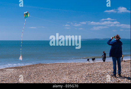 Man flying a kite on a beach at Bournemouth, Poole bay, Dorset, England, UK. - Stock Photo