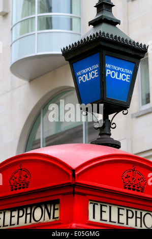 London, England, UK. Traditional red telephone box and blue Metropolitan Police lamp in Agar Street, by Zimbabwe - Stock Photo