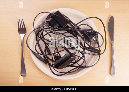 cable tangle on a plate symbolising the German term Kabelsalat (cable salad) also known as spaghetti syndrome - Stock Photo
