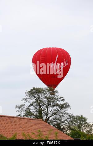 Earswick, York, UK. 3 May 2014.  Virgin hot air balloon passing overhead in Earswick, York then landing close to - Stock Photo