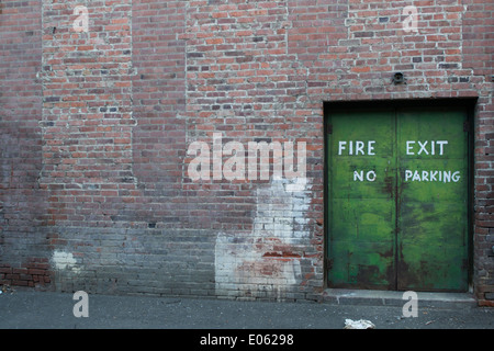 Fire exit, no parking doorway in a brick building to an alley - Stock Photo