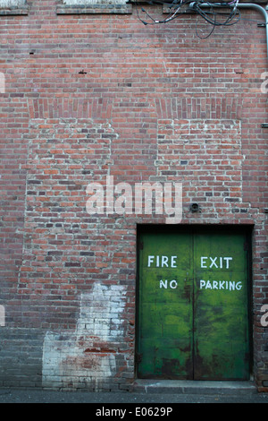 A fire exit doorway in a brick building leading to an alleyway. - Stock Photo
