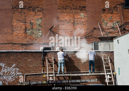 Workers clean mortar joints on a brick building. Strip District, Pittsburgh, Pennsylvania - Stock Photo