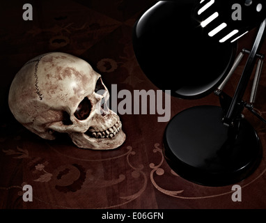 a model pirate skull on a table next to a lamp - Stock Photo