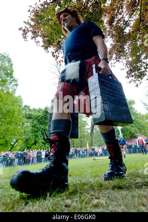 Peine, Germany. 04th May, 2014. A participant to the Highland Gathering carries two 75 kilogram weights during the - Stock Photo