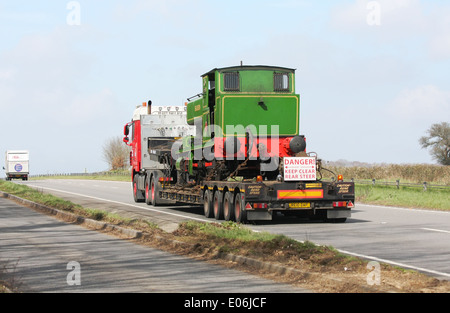 An articulated low loader hauling a train engine along the A417 dual carriageway in The Cotswolds, England - Stock Photo