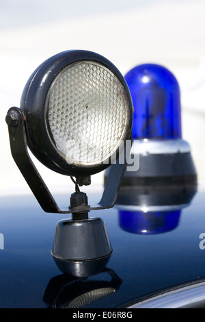 Spot Light and Blue police light on old classic Police car - Stock Photo