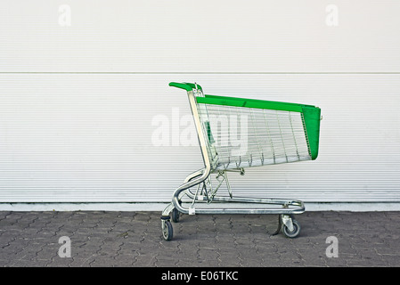 Empty Shopping Cart parked in front of large supermarket. Consumerism concept. - Stock Photo